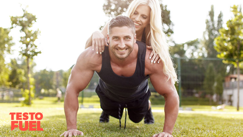 Strong and fit man doing press-ups with a woman on his back