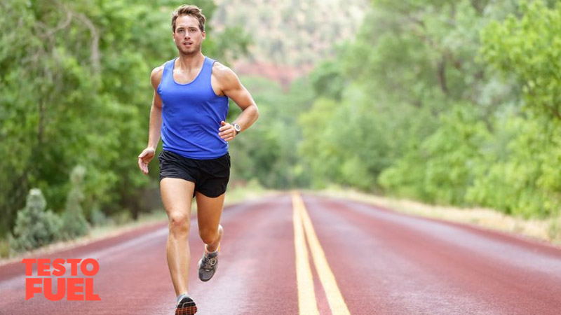 Athletic man running down the carriageway of a woody area