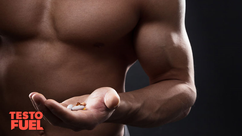 Bodybuilder with muscular arms holding a range of different pills and supplements
