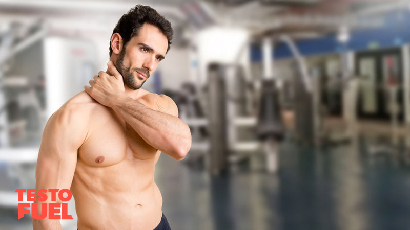 Athletic man holds his neck whilst in the gym in pain