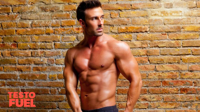 Athletic, toned bodybuilder with a six pack stood in front of a brick wall