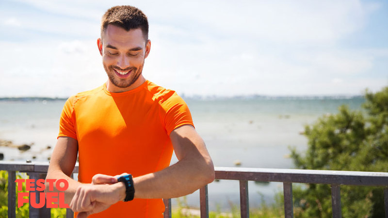 Athletic young runner wearing a heart rate monitor smiling on the beach