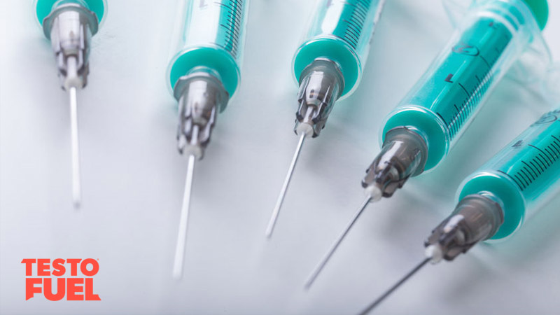 A range of needles / syringes laif out in a circle on a white background
