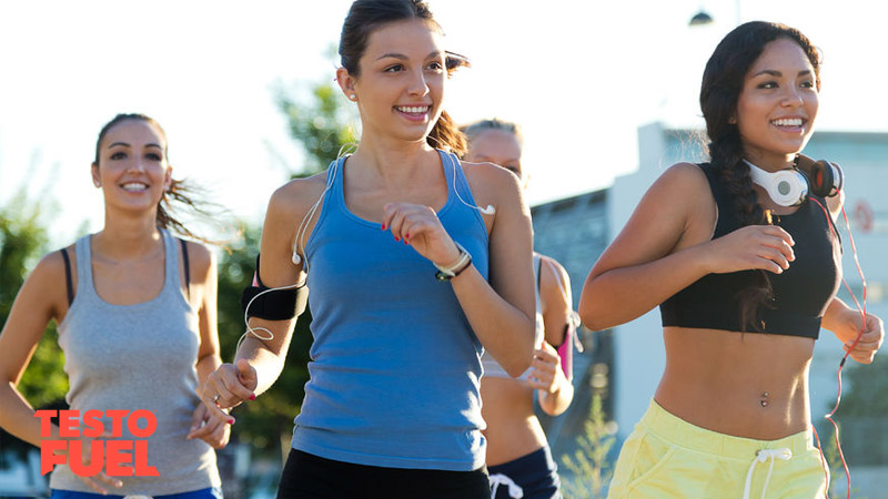 A small group of young, athletic women running outside
