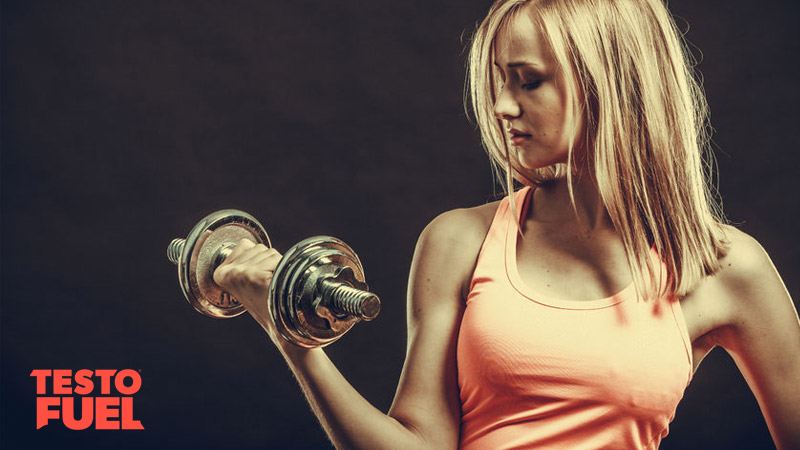 Blonde-haired woman lifting a dumbbell and wearing an orange vest