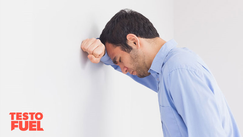 A middle-aged man leans against the wall with his head his hands