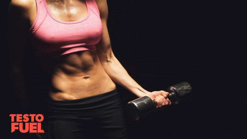 Woman in pink sports top lifting a weight as a bicep curl on black background