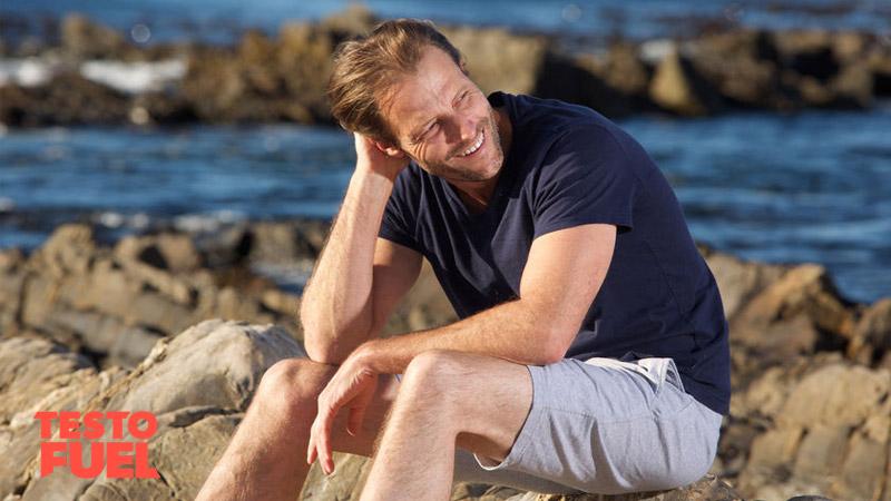 Older man sat at the beach smiling