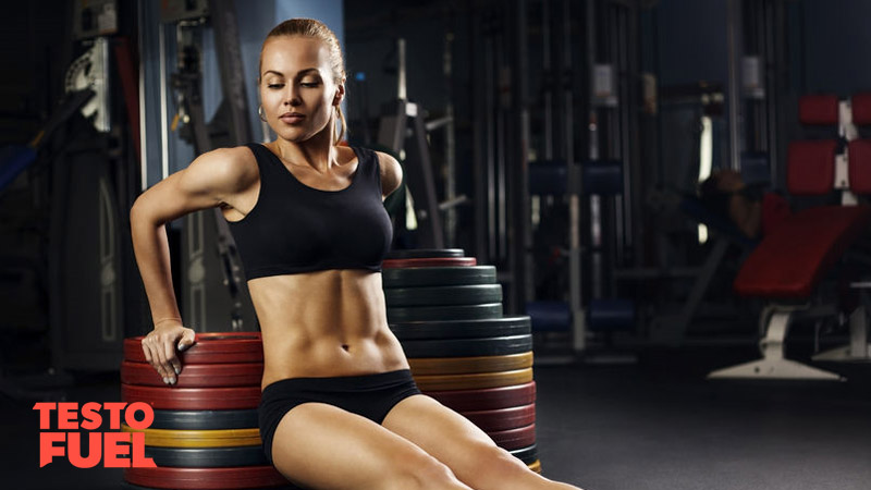 Muscular woman performing body weight dips off of some weight plates